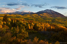 The Beckwith Mountains rise above a valley filled with green and golden aspens punctuated by the rust colors of scrub oak on Kebler Pass Road outside of Crested Butte, Colorado.