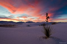 The setting sun turns the skies and sand shades of pink at White Sands National Monument in New Mexico.