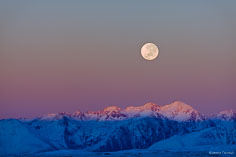 A full moon sets as the rising sun turns the snowy mountain landscape pink and violet on the South Island in New Zealand.