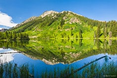 The vibrant colors of East Beckwith Mountain are reflected in the calm waters of Dollar Lake in western Colorado.
