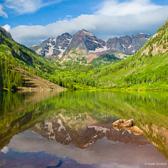 The Maroon Bells and the surrounding vibrant hillsides reflect in Maroon Lake outside of Aspen, Colorado.