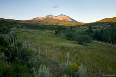 Mt. Sopris is lit by the rising sun behind a ranch view outside of Basalt, Colorado.