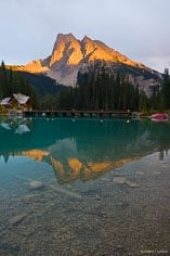 The setting sun breaks through the clouds and shines on Mt. Burgess reflected in Emerald Lake in Yoho National Park, Canada.