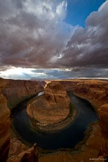 The sun breaks through foreboding storm clouds and lights the walls of the canyon at Horseshoe Bend outside of Page, Arizona.