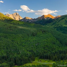 The last light of the day glows on Capital Peak beyond a luch green valley filled with aspen trees outside of Basalt, Colorado.