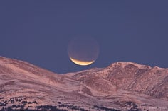 During a lunar eclipse, a sliver of the full moon remains exposed as it sets over the Rocky Mountains outside of Buena Vista, Colorado.