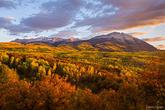 The Beckwith Mountains catch rays from the setting sun behind a valley filled with autumn colors outside of Crested Butte, Colorado.