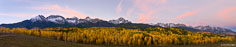 Early on a fall morning, dawn light turns the clouds pink above Mount Sneffels and the Sneffels Range in this panoramic view outside of Ridgway, Colorado.