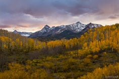 A fall scene in southwestern Colorado with a setting sun illuminating breaking cloud cover over the Sneffels Range outside of Ridgway.