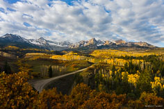 Early morning cloud cover breaks and sunshine spills into a valley filled with golden aspens beneath the Sneffels Range outside of Ridgway, Colorado.