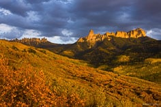 The setting sun breaks through clouds and bathes Chimney Rock, Courthouse Mountain, and the valley filled with autumn colors below with golden light outside of Ridgway, Colorado.