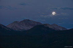 The full moon sets over Mount Yale in the purple skies of twilight outside of Buena Vista, Colorado.