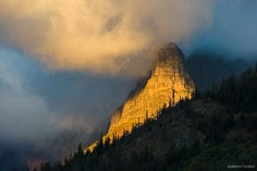 A shaft of light streams through swirling clouds and illuminates the side of Pumpelly Pillar at sunrise in Glacier National Park, Montana.