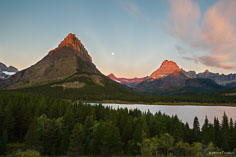 The first rays of sunlight strike the tops of Grinnell Point and Swiftcurrent Mountain as the full moon sets between them at Swiftcurrent Lake in Glacier National Park in Montana.