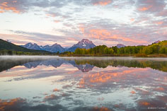 Mount Moran and a sky filled with glowing pink clouds at sunrise are reflected in the calm waters of the Snake River at Oxbow Bend in Grand Teton National Park, Wyoming.