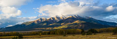 Overnight storm clouds begin to clear shortly after sunrise revealing a dusting of snow on the top of Mt. Princeton outside of Buena Vista, Colorado.