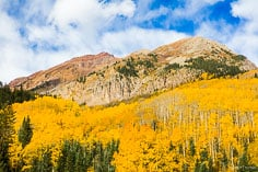 Puffy white clouds fill a Colorado blue sky above Leahy Peak flanked by golden aspen trees outside of Aspen, Colorado.