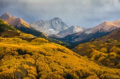 The sun breaks through evening storm clouds and illuminates a valley carpeted in golden aspen trees beneath Capitol Peak outside of Snowmass, Colorado.