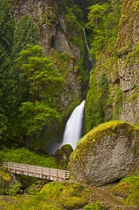 A foot bridge crosses in front of Wahclella Falls in the Columbia Gorge, outside of Portland, Oregon.