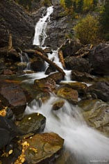 A fall rain shower adds to the flow of water down Umcompaghre Falls outside of Ouray, Colorado.