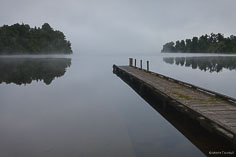 Early morning fog lifts off of Lake Mapourika on the South Island of New Zealand.