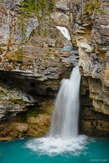 The rushing Beauty Creek drops over one of the many waterfalls on it's drop through a limestone walled canyon in Jasper National Park in Alberta, Canada.