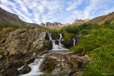 First light shines on the San Juan Mountains above a small waterfall in American Basin in southwestern Colorado.