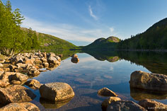 The rocky shoreline of Jordan Pond directs your view to The Bubbles reflecting in the calm water at Acadia National Park in Maine.
