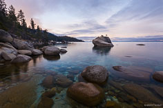 The pink skies of dawn reflect in the calm water around Bonsai Rock at Lake Tahoe in Nevada.