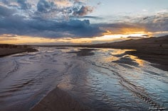 Medano Creek flows past the Great Sand Dunes towards the San Luis Valley at sunset in southern Colorado.