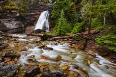Baring Creek gently flows over Baring Falls and glides down a streambed sprinkled with red rocks on its way down to Saint Mary Lake in Glacier National Park in Montana.