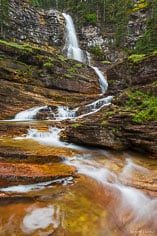 Virginia Falls twists and turns its way down a red rock wall on its journey to meet up with the Saint Mary River in Glacier National Park, Montana.