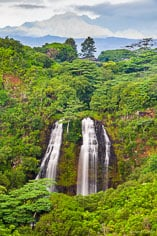 The Mahaleha Mountains emerge from rain clouds behind Opaekaa Falls dropping into a lush valley in Kauai, Hawaii.