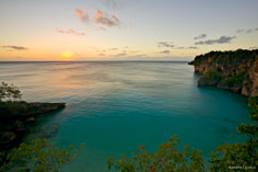 The sun sets on the horizon over calm seas at Little Bay in Anguilla, BWI.