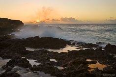The sun sets on the horizon behind crashing waves at Blolly Ham Bay in Anguilla, BWI.