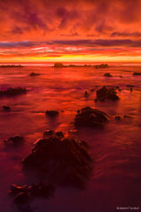 The sun rising over the horizon turns the sky shades of orange and red that are reflecting in the rocky waters along the coast of South Island, New Zealand.
