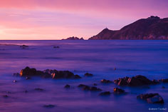 Sunrise turns the skies and the sea pink with the Nugget Point Lighthouse perched on the point in the distance at Kaka Point on the South Island, New Zealand.