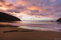 Rain clouds break up and take on glorious pastel shades at dawn at Whites Bay in New Zealand.