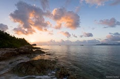 The rising sun lights the clouds and bathes Forest Bay in pastel colors in Anguilla, BWI.