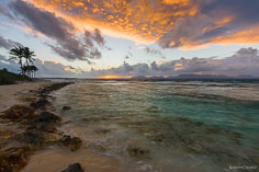 The clouds take on an orange glow as the sun rises above the horizon at Merrywing Bay in Anguilla, BWI.