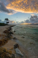 The clouds light up as the sun rises above the horizon at Merrywing Bay in Anguilla, BWI.