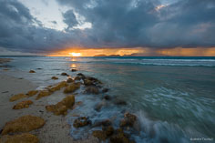The rising sun pierces through a break in the clouds at Merrywing Bay in Anguilla, BWI.