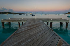 The full moon sets in the distance as seen from a pier on Road Bay in Aguilla, BWI.