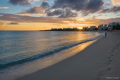 A person strolls the beach as the sun sets on the horizon at Shoal Bay West in Anguilla, BWI.