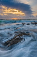 Waves crash into a rocky beach at sunrise in Coral Cove State Park, Florida.
