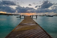 The setting sun glows on the horizon off the end of a pier in Road Bay, Anguilla.