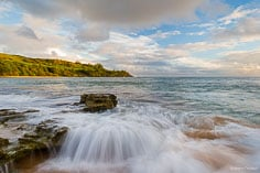 Waves rush into the rocky shoreline in Moloaa Bay as the early morning light illuminates the lush green hillside in the distance on the northeast coast of Kauai, Hawaii.
