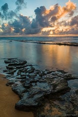 The sun rises behind a bank of clouds, filling the sky with golden light and reflecting in a pool along a rocky shoreline on Waipouli Beach in Kauai, Hawaii.