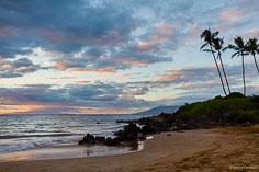 The setting sun bathes the island of Lanai and the clouds above in golden light as seen from Polo Beach in Maui, Hawaii.