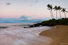 Pink skies at daybreak illuminate the gently breaking waves along the shore of Polo Beach in Maui, Hawaii.